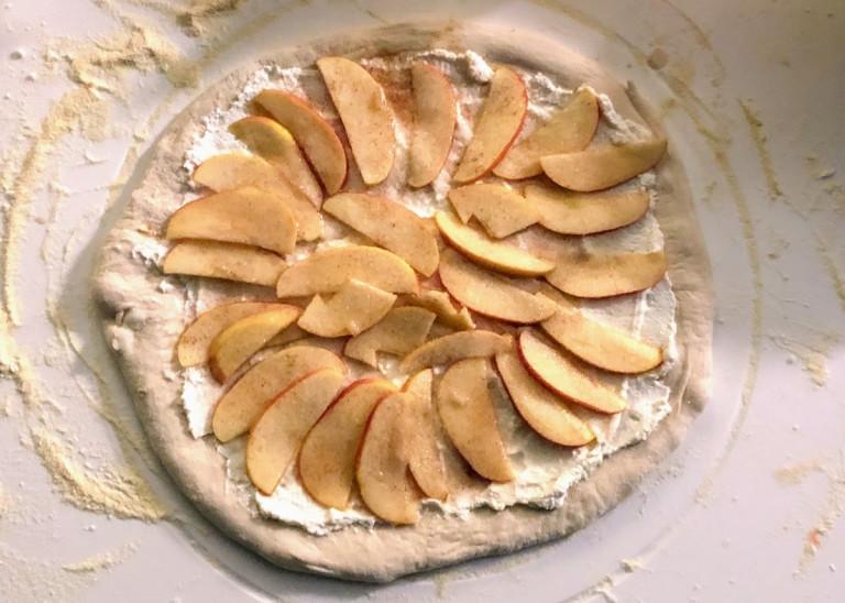 Abbildung einer belegten, noch nicht gebackenen Apfel-Zimt-Ricotta-Pizza